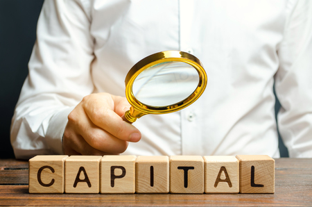 Businessman exploring the origin of capital. The combination of material, intellectual and financial resources used for profit, additional material benefits. Concept of business and finance