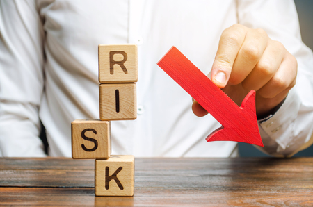 Wooden blocks with the word Risk and a down arrow. Reduce financial risk for investment and capital. Protection of investment funds and assets. Deposit insurance. Debt restructuring.