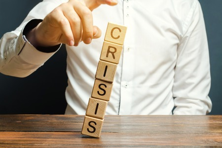 Businessman removes wooden blocks with the word Crisis. The exit from the crisis and financial stability. Focus on resolving the midlife crisis. The rise of the economy and business development. Imagens