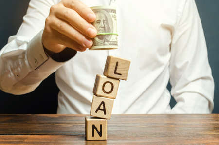 Man holds dollars in hands over the word Loan. The concept of paying a loan for housing. Bank, commercial and consumer credit. Mortgage interest rates repayment.
