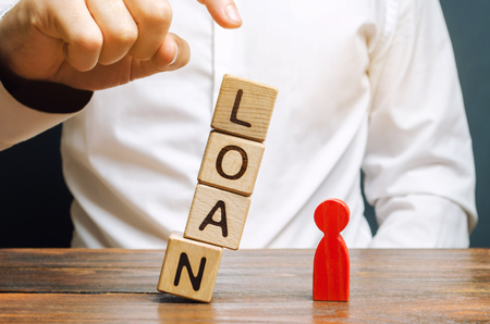 Wooden blocks with the word Loan fall on a miniature person. The concept of large lending rates for property and business. Lending market. Bank, commercial and consumer credit. Real estate