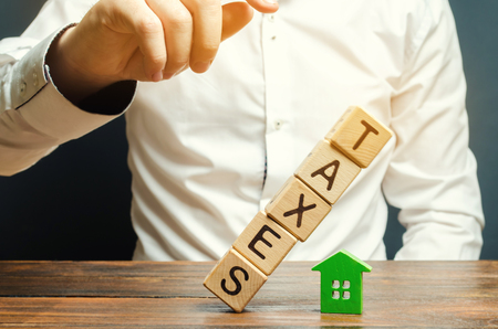 Wooden blocks with the word Taxes fall on a miniature house. The concept of the tax burden on housing, apartment, property. Mortgage. Taxation. Taxpayer. Commercial real estate. Soft selective focus Imagens