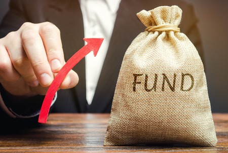 Money bag with the word Fund and up arrow. The concept of increasing the payroll. Investing in securities investors. Growing market value. Wealth, stability, safe investment. Financial resources Stock Photo
