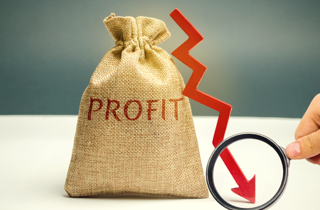 Bag with money and word profit and down arrow. Unsuccessful business and poverty. Profit decline. Loss of investment. Low wages. Economic crisis. The fall of the financial market Stock Photo