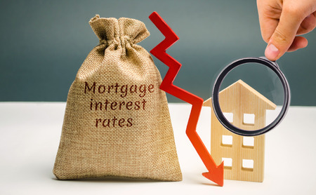Bag with the money and the word Mortgage interest rates and arrow to down and house. Low interest in mortgages. Reducing interest payments for mortgages. The fall in housing rates on credit. Low housing demand Foto de archivo