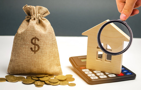 Bag with money and dollar sign and wooden houses. Financing in the country. Investing money in real estate. Saving and accumulation of money. Mortgage. Buying a home. Property sale. City budget. Imagens