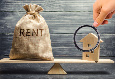 Money bag with the word Rent and a wooden house on the scales. The concept of payment for rental housing. Debt repayment. To renting a house. Rent a property. Court, Law and Justice