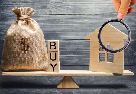A money bag and wooden blocks with the word Buy and a miniature house on scales. The accumulation of money for the purchase of real estate. Buying a home. Buy a property. Reaching the goal. Foto de archivo - 124957830