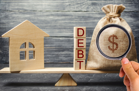 Money bag and wooden blocks with the word Debt and a miniature house on the scales. Payment of debt for real estate. Pay off the mortgage loan. Risks of buying a house. Buying an apartment on credit. Banco de Imagens