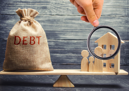 Money bag with the word Debt and a miniature house with a family on the scales. Payment of debt for real estate. Pay off the mortgage loan. Risks of buying a house. Buying an apartment on credit
