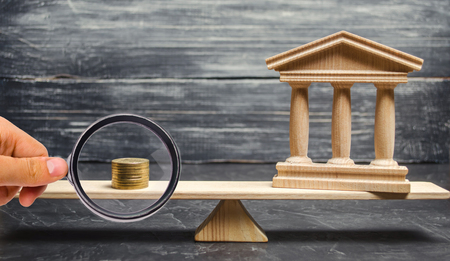 A miniature bank and money on the scales. The concept of successful investment in the bank. Credit  Loan  Deposit.The concept of dividend payments. Banking system, investment in the economy Stock Photo