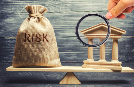 A money bag with the word Risk and a bank building on the scales. The concept of financial and economic risk. Unreliable investment. Unpaid loan. Financial risk management. Commercial loan Stock Photo