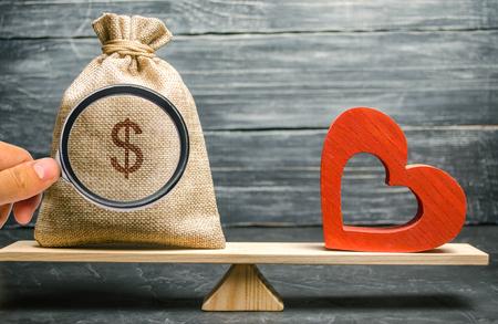 Bolsa con dinero y corazón de madera rojo en la balanza. Dinero versus concepto de amor. Pasión versus lucro. Elección de familia o carrera. Psicología familiar. Mente contra pasión