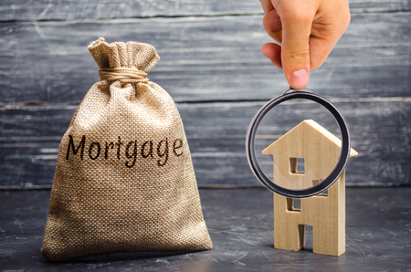 A bag with money and the word Mortgage and a wooden house. The accumulation of money to pay interest rates on mortgages. Buying a property in debt. Take credit for housing. Imagens
