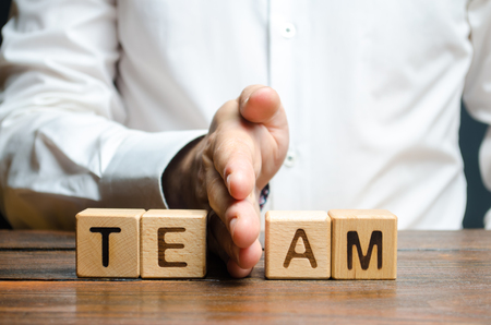A man shares with his hand cubes with the inscription team. Dividing the collective into two parts or disbanding the team. Lack of leadership qualities and poor quality of business management. Stock Photo