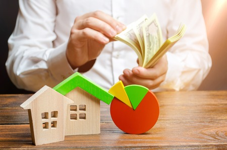 Houses with pie charts and a man counting money. Research of the real estate market and price trend. Budget, maintenance costs, utilities, bills. Energy efficiency, emissions. Business planning Stock Photo