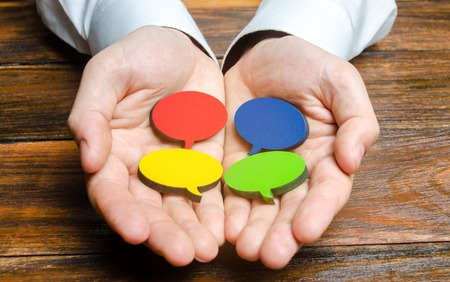 Man holds multicolored speech bubbles in his hands. Listen to other opinions and points of view, accepting criticism and comments. Reverse contact with customers and buyers. Freedom of speech. Imagens