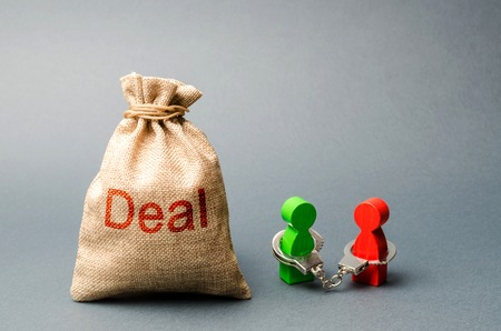 Two people are handcuffed to each other and stand next to the bag labeled Deal. Unclosed obligations between two persons, financial or moral debt. refusal to return debts. redemption and restructuring