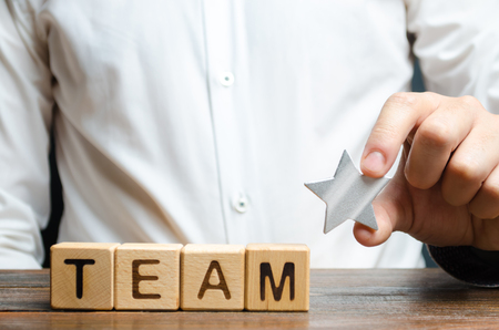 Businessman hands a star to the team near the inscription Team on the cubes. concept of recognition of the success and achievements of the group of employees, awarding. Encouraging workers
