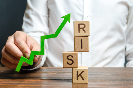 Businessman holding a green up arrow near the word Risk. Improving business resilience, reducing risks and costs. Development and strengthening of financial and economic systems. Business strategy.