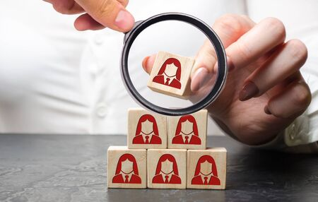 Businesswoman puts wooden blocks with the image of female employees. The concept of management in a team. Human resources. Womens team. Hiring workers. Dismissal. Headhunting. Human resources Banco de Imagens