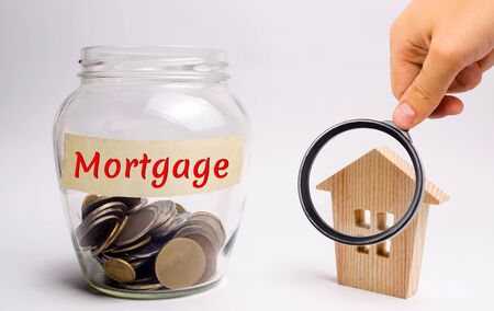 A glass jar with money and the word Mortgage and a wooden house. The accumulation of money to pay interest rates on mortgages. Buying a property in debt. Take credit for housing. Mortgage tax.