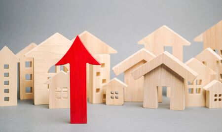 Red arrow up and miniature wooden houses. The concept of rising property prices. High mortgage rates. Expensive rental apartment. Growing demand for home purchase. Population growth in the city.