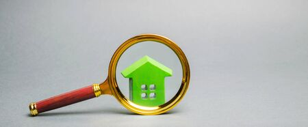 Magnifying glass and miniature wooden house. House searching concept. Home appraisal. Property valuation. Choice of location for the construction. Search for housing and apartments. Real estate