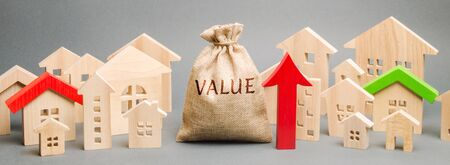A money bag with the word Value, wooden houses and an up arrow. Concept of real estate market growth. High rental and mortgage rates. The concept of increasing housing prices. Rising rent.