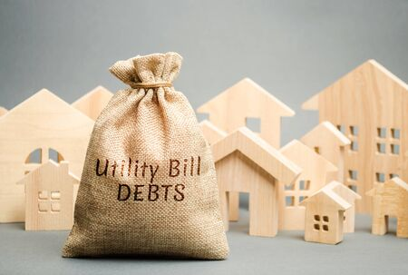 Money bag with the words Utility bill debts and wooden houses. Fines and penalties for failure to pay the debt for electricity and gas. Register of debtors. Stopping the provision of utilities. Foto de archivo