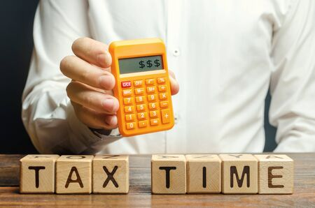Wooden blocks with the word Tax time and taxpayer with a calculator. The concept of paying the tax rate. Taxation / burden. Pay off debts. Property / income annual taxes. Dollars on the screen 版權商用圖片
