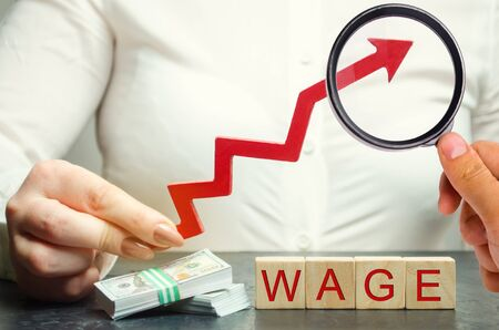 Female hand holds arrow up above word wage. Increase of salary, wage rates. Promotion, career growth. Raising the standard of living. Increase profits and family budget. Wooden blocks Stock Photo