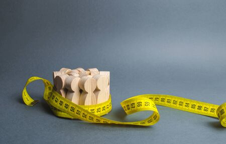 A crowd of wooden figures Gripped by measuring tape. Information statistics, measurement of the number, trends of population growth. Social Sciences. Promotion of ideas for weight loss, lifestyle
