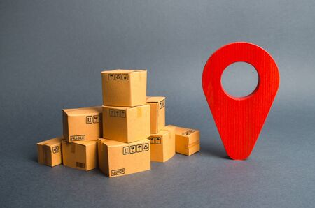 A pile of cardboard boxes and a red position pin. Locating packages and goods. Algorithm for constructing a minimum route for the delivery of orders. Tracking parcels via the Internet.