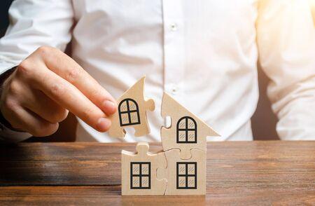 Un homme collectionne une maison de puzzles. Construction de votre propre immeuble résidentiel. Prêt hypothécaire, agrandissement résidentiel et amélioration des conditions de vie. Créer une famille. Le concept de stabilité