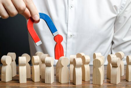 businessman pulls out a red figure of a man from the crowd with the help of a magnet. toxic, uncompetent worker. Increase team efficiency, productivity. leader manages the business and forms a team.