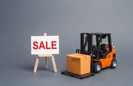 Orange Gabelstapler trägt einen Karton und einen Ständer mit einem Wortverkauf. Wachstum des Umsatzes. große Rabatte auf Waren der ausgehenden Saison. Warenaustausch mit anderen Ländern. Käufer anziehen Standard-Bild