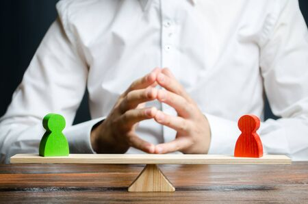 A man with hands in the lock and looks at the rival red and green figures on a scales. The concept of conflict resolution and the search for a compromise in the dispute. Weighted decision