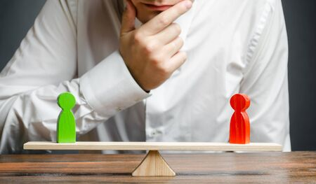 Man holds hand on chin looks at the rival red and green figures on a scales. Weighted decision. The concept of conflict resolution and the search for a compromise in the dispute.