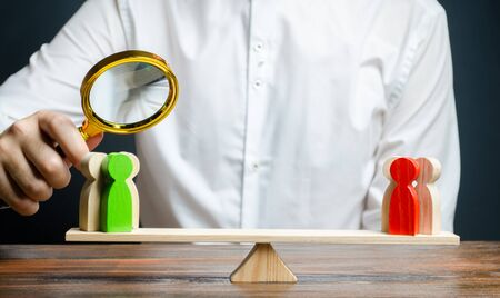 A man with a magnifying glass is looking at the rival red and green figures groups on scales. conflict resolution and the search for a compromise in the dispute. Research argument of each side
