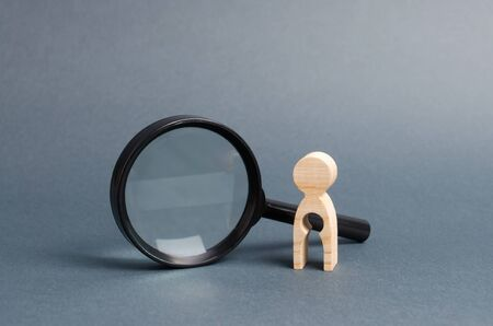A wooden figure with a baby-shaped void stands near a magnifying glass. concept of infertility and women and the inability to have children. Abbort, the loss of a child. Treatment and Prevention