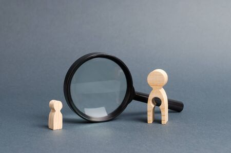 A wooden figure of a woman with emptiness and a child stands near the magnifying glass. The concept of finding a child, the adoption of children. Mother lost her baby and is now looking for him.