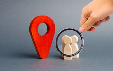 Magnifying glass is looking at people are standing near the location marker. Concept of navigation and venue. Tourism and travel. Orientation around the city, location of events