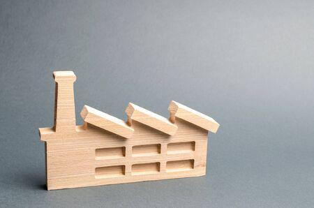 Holzfigur einer Pflanze oder Fabrik auf grauem Hintergrund. Recycling von Rohstoffen. Das Konzept von Industrie und Produktion.Investitionen in den Bau neuer Fabriken.