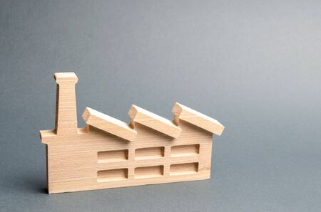Wooden figurine of a plant or factory on a gray background. Recycling raw materials. The concept of industry and production.Investments in the construction of new factories.