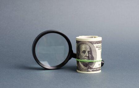 Lupe und ein Bündel Geld. Konzept der Mittelbeschaffung, das Anziehen von Investitionen. Kredit auf Gehaltsscheck, dringende Kredite. Das Studium der Gewinnquellen, Geldwäsche, Offshore. Finanzüberwachung