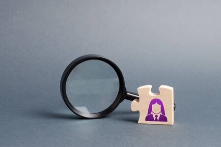 Puzzle with business woman symbol and magnifying glass. search for a new employeeor element in the general plan or strategy. Business planning, information gathering. Key employee.