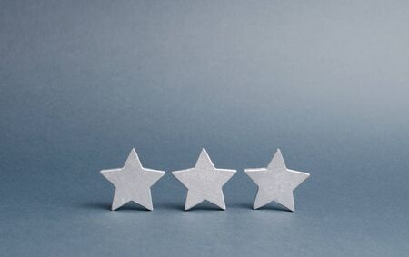 Three stars on a gray background. The rating of the hotel, restaurant, mobile application. Quality service, buyer choice. Success in businessThe concept of rating and evaluation.