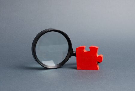 Red puzzle and magnifying glass. The concept of finding the missing detail or element in the general plan or strategy. Business planning, information gathering. Controlling stake. Key employee. Imagens
