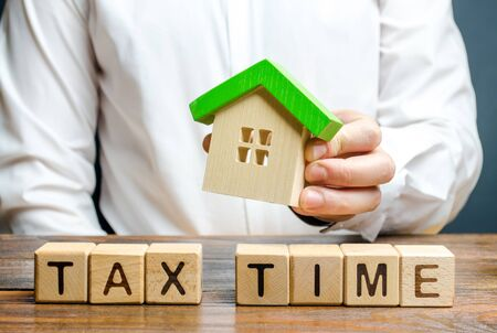A man holds a figure of a house above the inscription Tax Time. Taxation, income tax. Declaring income, countering the shadow economy, digitalization of the economy. New rules for business.